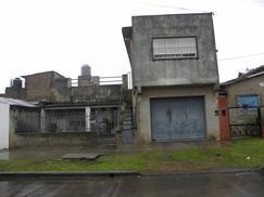 Casa de material con techo de losa con garage, alero, 3 dormitorios; baño; living comedor: escalera