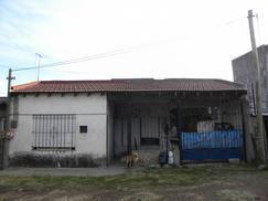 Casa de material con techo de losa y parte de tejas.